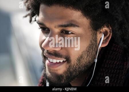 Portrait of smiling man écouter de la musique sur ses écouteurs Banque D'Images