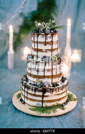 La cuisine, douceur, concept de mariage. fermer jusqu'à trois niveaux de l'étonnant gâteau avec streeps blanc et Banque D'Images