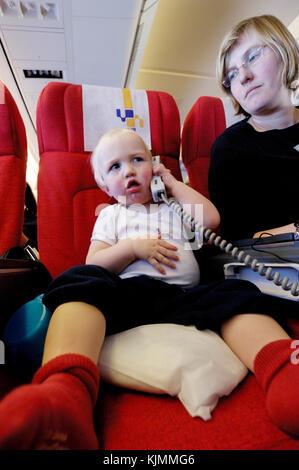 Mère et 1,5 ans baby boy Henry avec l'unité de commande audio / vidéo et téléphone satellite sur un vol long courrier Banque D'Images
