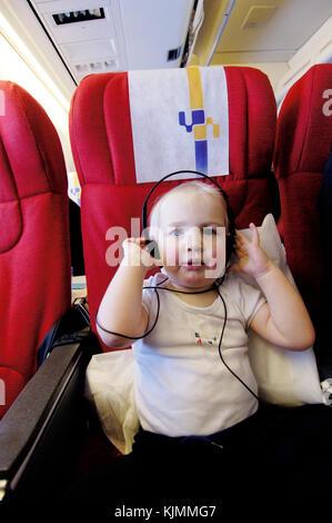 1,5 ans baby boy Henry portant des écouteurs sur un vol long courrier dans l'économie classes LGW-ANU Banque D'Images