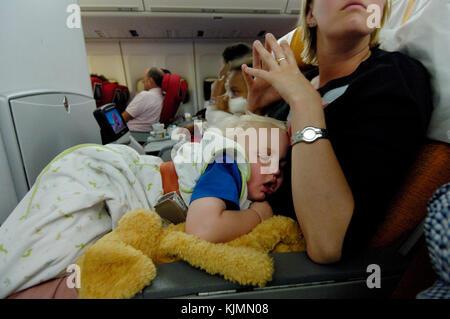 Un jeune enfant endormi sur les genoux d'une femme dans la cabine de classe économique d'un Boeing 747-400 de Virgin Banque D'Images