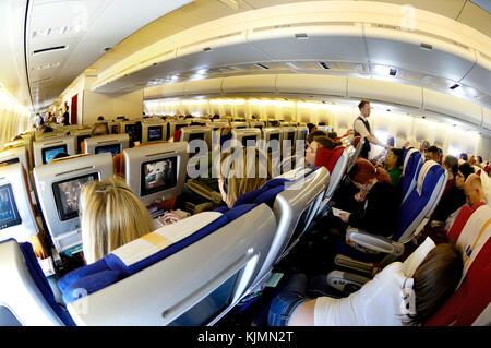Les passagers assis dans la cabine de classe économique sièges regarder les divertissements à bord d'un Boeing 747 Banque D'Images
