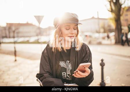 Belle fille de sms sur son téléphone portable dans les rues de la ville Banque D'Images