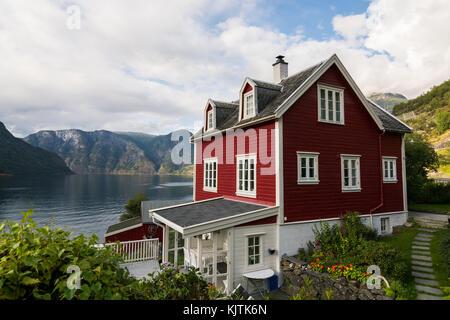 AURLAND, NORVÈGE - AOÛT 2017: maison en bois rouge debout sur le fjord Banque D'Images