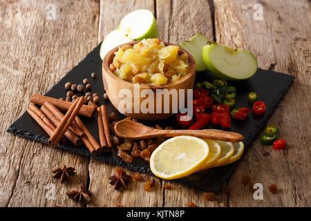 Chutney de pommes épicées avec des ingrédients close-up dans un bol sur la table rustique, horizontal. Banque D'Images