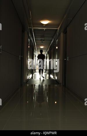 L'homme marchant dans un long couloir Banque D'Images