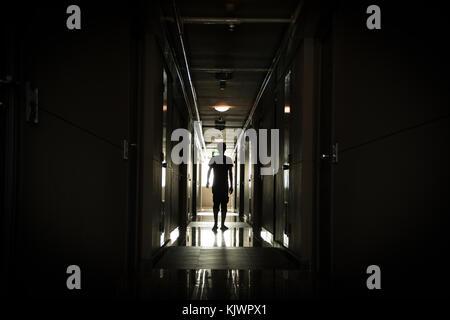 Homme marchant dans un long couloir sombre Banque D'Images