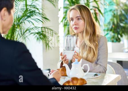 Portrait de jeune femme moderne de boire du café au café tableau entendre quelqu'un assis en face d'elle pendant Banque D'Images