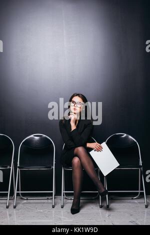 Beau costume female student holding fichier réunion assis sur une chaise et à la zone vide à la planification du Banque D'Images