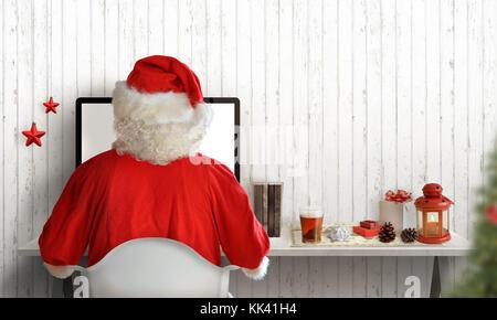 Père Noël travailler sur ordinateur et d'envoyer des lettres aux enfants. arbre de Noël, cadeaux, et décorations Banque D'Images