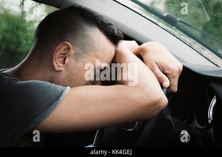 Closeup of a young caucasian man sitting at le siège conducteur d'une voiture couchée la tête sur le volant, dans Banque D'Images