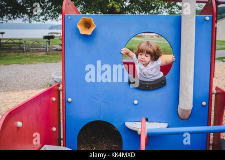 Une petite fille monte à l'équipement de jeu sur journée d'été Banque D'Images