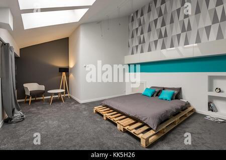 Gris et Blanc chambre avec lit papier peint à motifs et palettes Banque D'Images