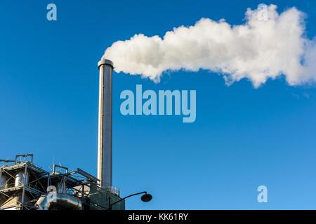 Fumeurs cheminée d'usine. La grande cheminée métallique d'une usine d'incinération est recracher un long nuage de Banque D'Images