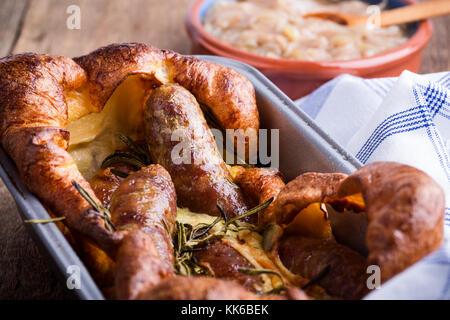Saucisses cuites dans yorkshire pudding batter et servi avec sauce à l'oignon, crapaud dans le trou Banque D'Images