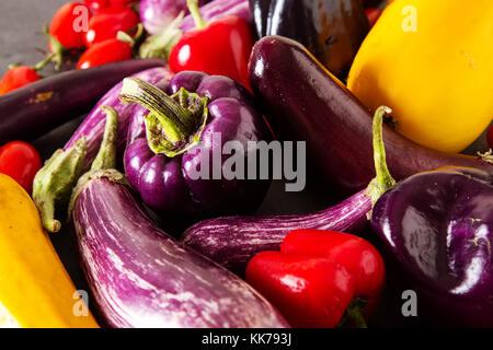 Petite aubergine, courgettes, tomates jaunes et violets poivre. arrière-plan foncé. La nourriture végétarienne du Banque D'Images