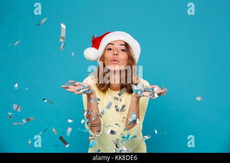 Close-up portrait of charming brunette woman in Santa's hat blowing confetti dans Appareil photo, isolé sur fond Banque D'Images