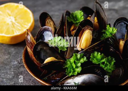 Moules à l'aide de fines herbes dans un bol en cuivre. Les fruits de mer. La nourriture au bord de la mer. fond Banque D'Images