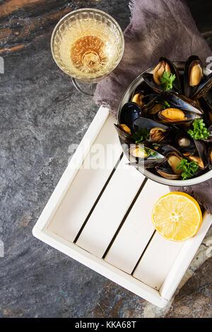 Moules à l'aide de fines herbes dans un bol avec le citron et le vin blanc sur une planche de bois. Les fruits de mer. La nourriture au bord de la mer. fond sombre