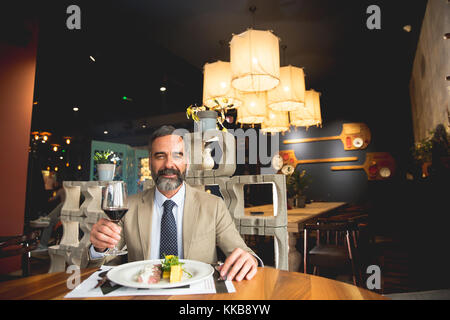 Handsome middle-aged businessman having lunch et drinking red wine in restaurant Banque D'Images