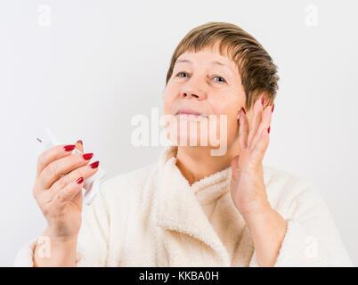 Grand-mère pousse une crème à mains Banque D'Images