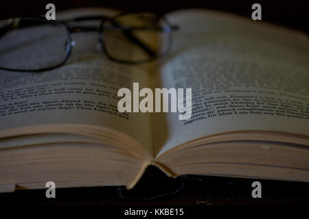 Une paire de lunettes de lecture reposant sur un vieux livre ouvert Kiplling, suggérant une personne âgée en prenant une pause de lecture
