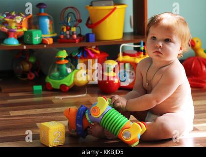 Mignon petit bambin avec ginger hair assis sur le sol au milieu des jouets en plastique holding dog dans les mains. Banque D'Images