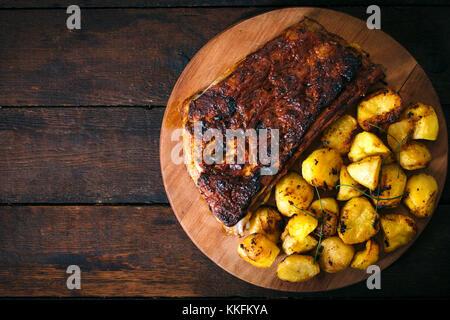 Pommes de terre au four et côte de boeuf dans la sauce barbecue de dessus sur fond de bois.blan l'espace sur le Banque D'Images