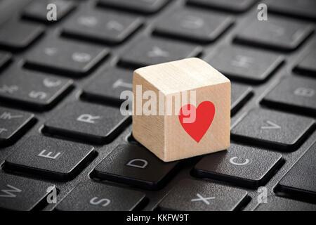 Bloc en bois avec forme de coeur rouge sur le clavier d'ordinateur portable. Banque D'Images