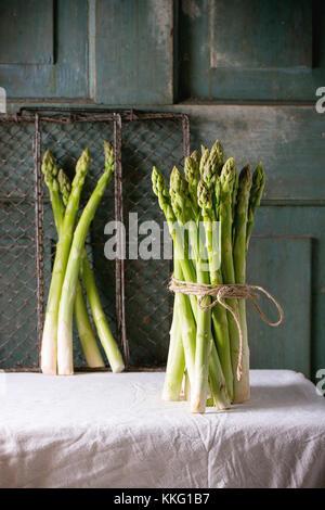 Ensemble d'asperges vertes sur nappe blanche avec fond en bois turquoise foncé atmosphère rustique. Banque D'Images
