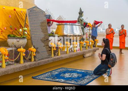 Bangkok, Thaïlande. Wat Saket (Phu Khao Thong), le Mont d'or. Femme prie comme moines donateurs principaux autour Banque D'Images