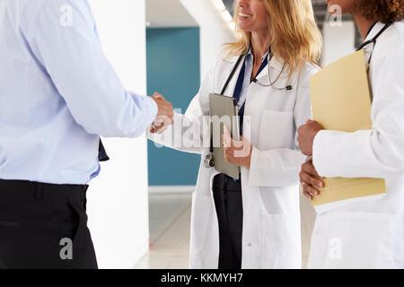 Trois médecins, hommes et femmes se serrer la main, mid section Banque D'Images
