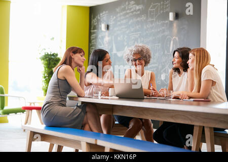 Les collègues de travail des femmes à l'aide d'ordinateur portable dans une réunion informelle Banque D'Images