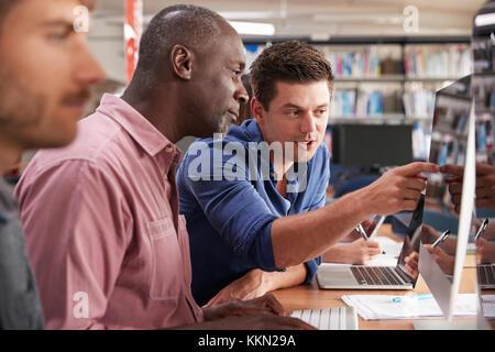 Mâle mature student avec tuteur l'acquisition de compétences en informatique Banque D'Images
