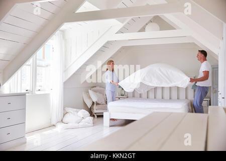 Couple Wearing Pyjamas faisant lit dans la matin Banque D'Images