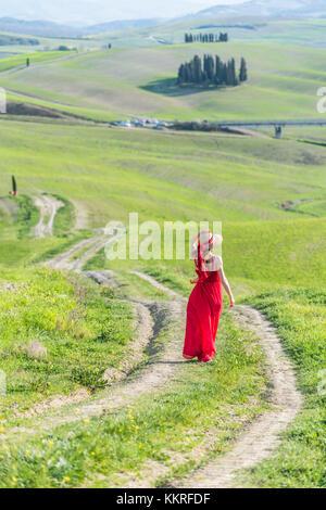 San Quirico d'orcia, Val d'orcia, Sienne, toscane, italie. Une jeune femme en robe rouge marcher le long chemin Banque D'Images