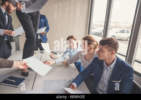 Professionnels des gens d'affaires qui ont réussi à avoir du plaisir bureau documents jetant Banque D'Images