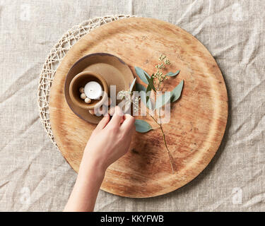 L'organisation de la main une bougie et simple d'un décor élégant avec des perles en bois et de feuilles sur une Banque D'Images