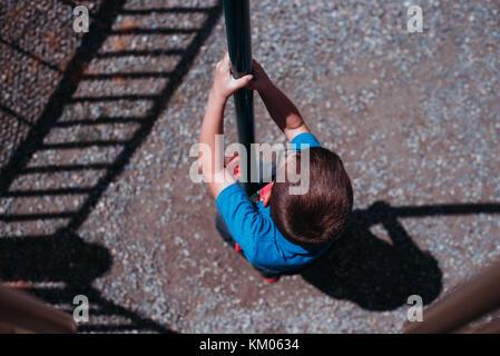 Un enfant glisse vers le bas d'un pôle à l'aire de jeux.