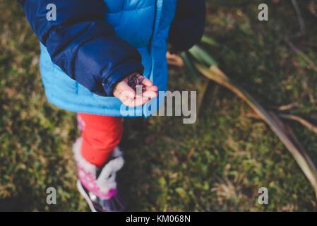 Une petite fille tenant dans ses mains les vers de terre. Banque D'Images