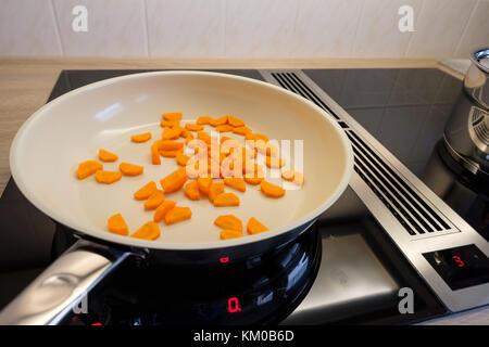 Les carottes dans une casserole sur une cuisinière à induction en vue de côté