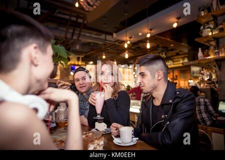 Jeune femme à boire le lait frappé alors qu'il était assis avec des amis au café Banque D'Images