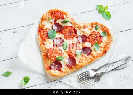 Pizza en forme de coeur sur fond de bois avec copie espace. pizza au pepperoni, tomates, fromage mozzarella et basilic Banque D'Images