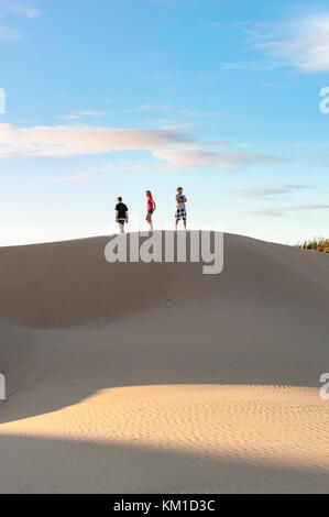 Trois adolescents marche sur le bord de dunes de sable de l'Oceano Dunes State Vehicular Recreation Area, Oceano Banque D'Images