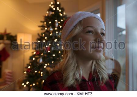 Curieux girl looking out window près de l'arbre de Noël la veille de Noël Banque D'Images