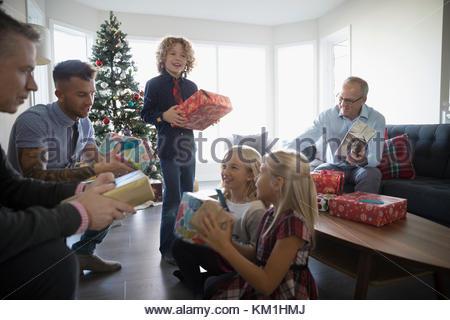 L'ouverture de la famille cadeaux de Noël dans la salle de séjour Banque D'Images
