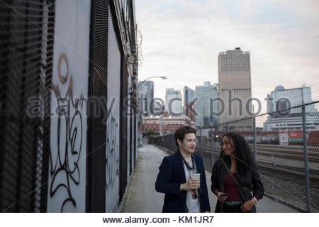 Jeune couple en train de marcher le long des voies de chemin de fer urbain Banque D'Images