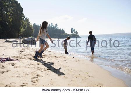 Garçon et fille amis jouant sur la plage de l'océan ensoleillé Banque D'Images