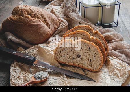 Une belle miche de pain au levain de blé blanche sur une plaque sur un bord du linge. Des pâtisseries maison.