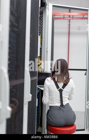 Portrait de technicien travaillant sur ordinateur portable en salle serveur Banque D'Images